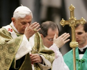 Pope Benedict XVI making the sign of the Cross during mass.